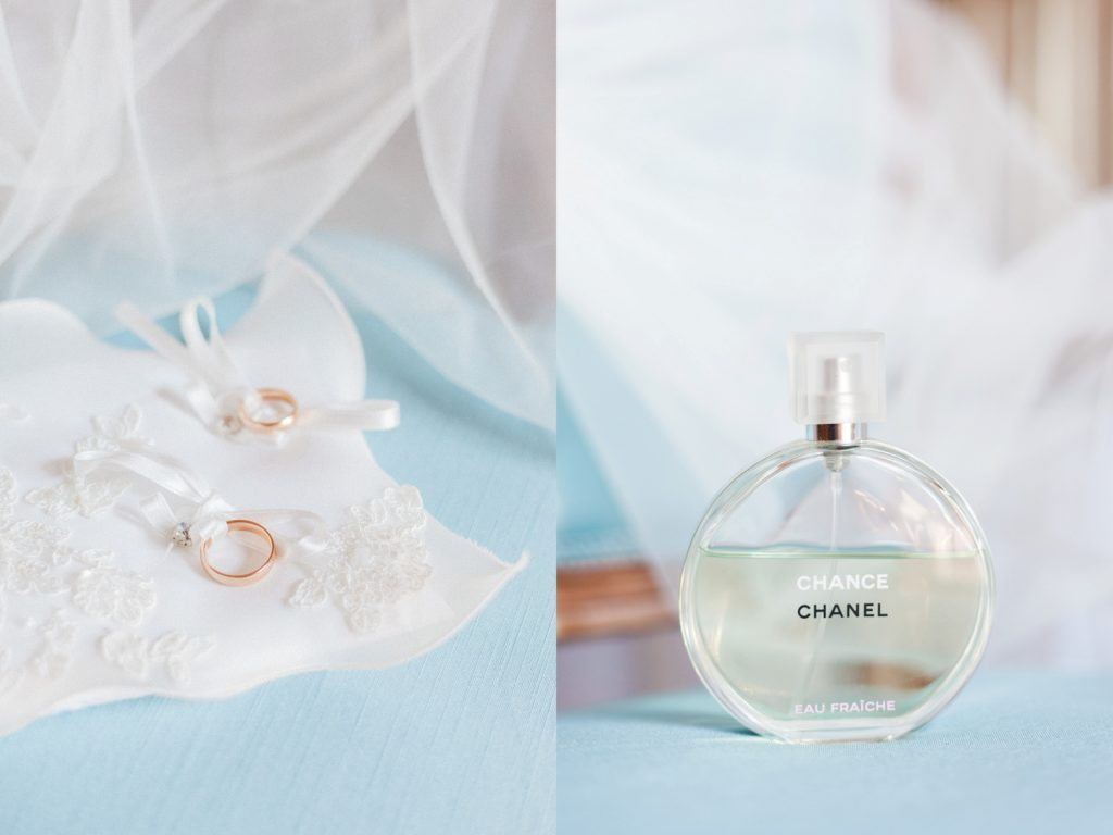 The couples gold wedding bands on a cushion and the brides Chanel Chance fragrance