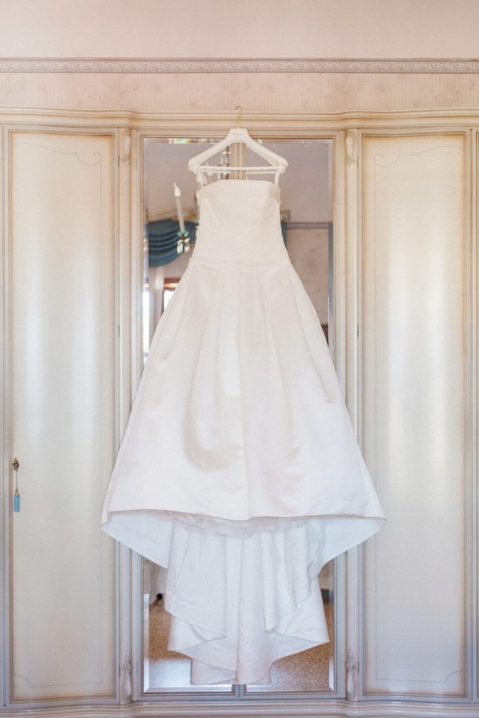 Italian brides beautiful white Pronovias gown hanging in her bedroom on the morning of her wedding