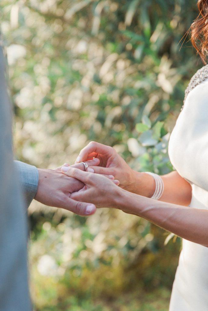 Couple exchange wedding bands during their destinaton wedding in Sivota