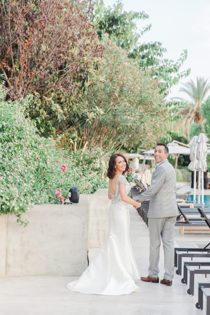 Newly married couple smile as they walk alongside the pool at Domotel Agios Nikolaos in Sivota