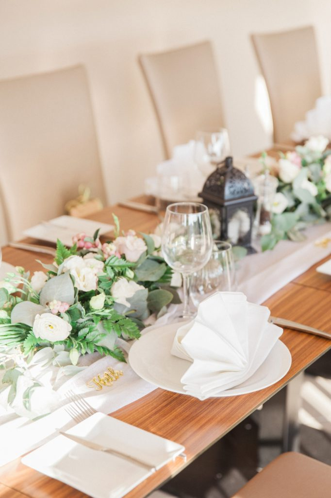 Wedding table decor featuring white and pink flowers, eucalyptus and small black lanterns