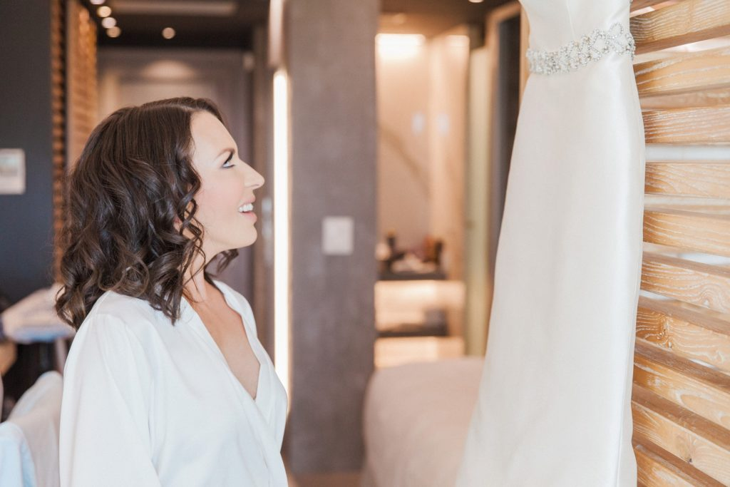 Bride smiles up at her Rosa Clara wedding dress before she puts it on