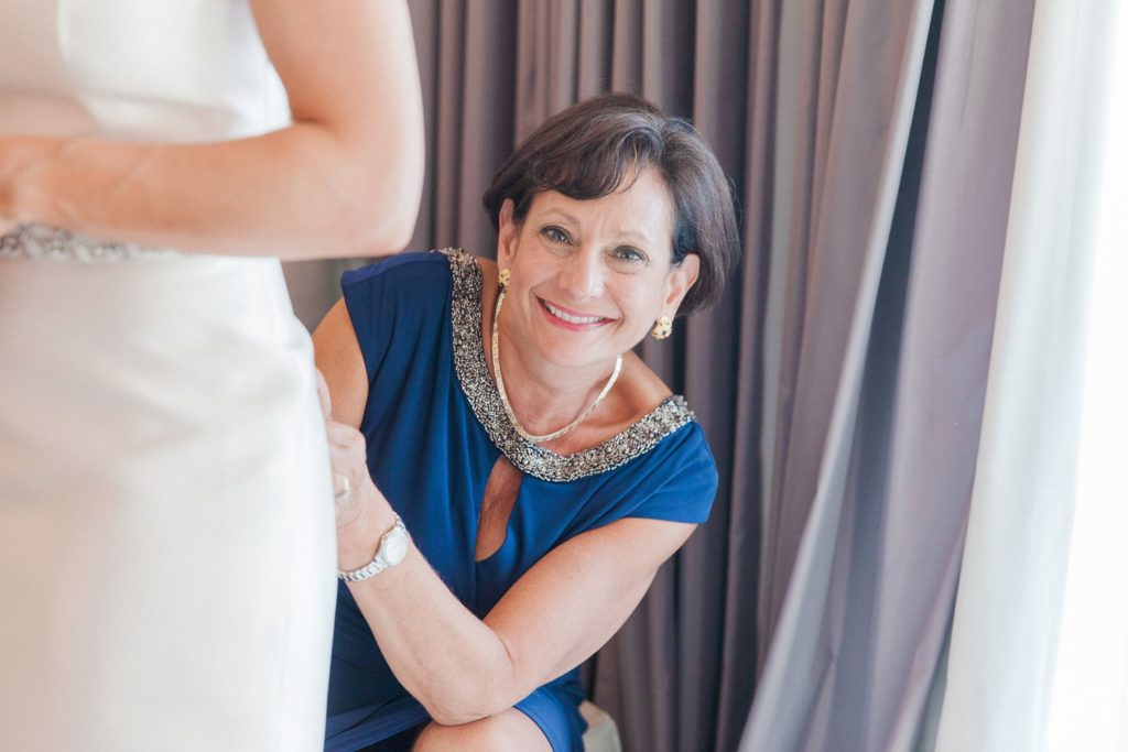 Wedding guest smiles as she helps the bride do up the buttons of her wedding dress