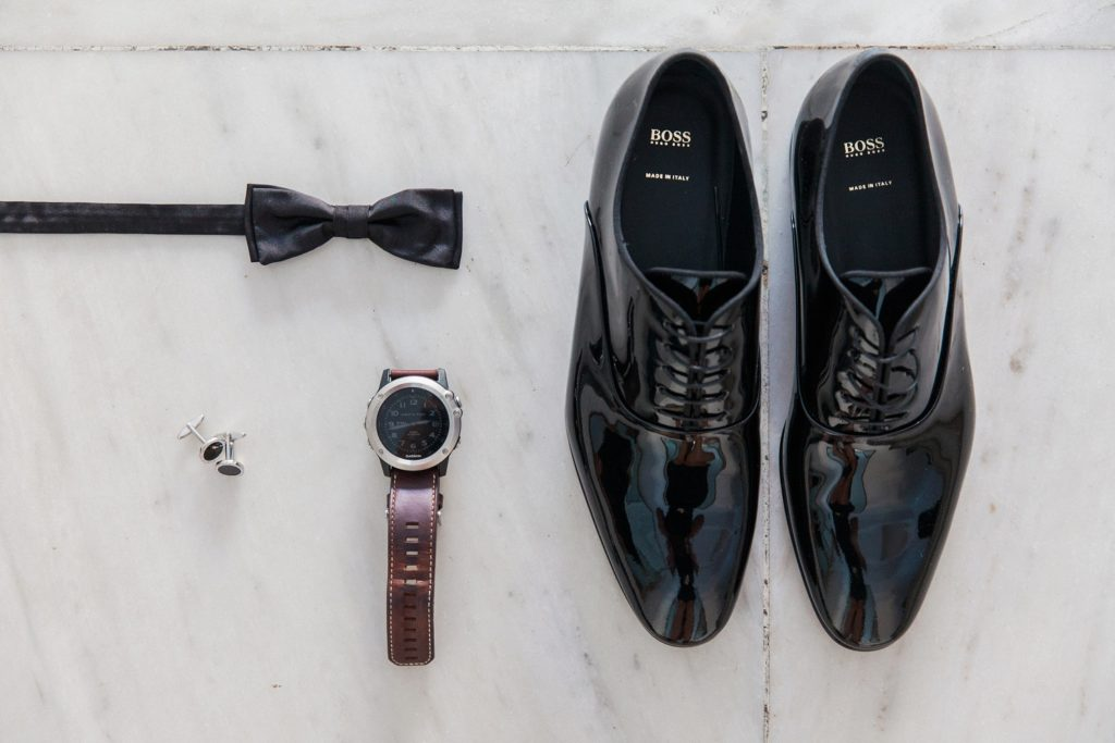 Flatlay of the grooms details featuring a bowtie, Boss shoes, cufflinks and watch