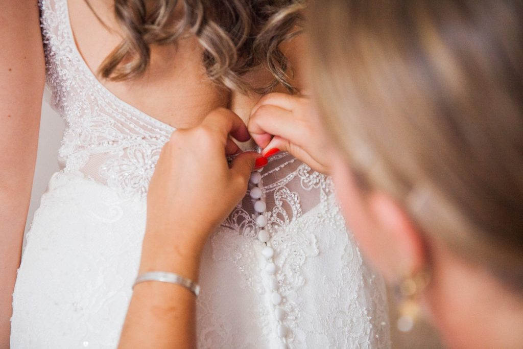 Guest helps bride do up her buttons on the morning of her wedding