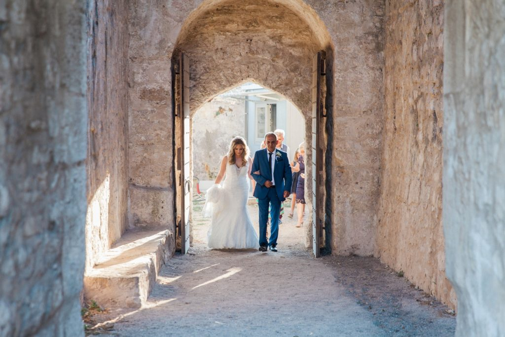 Bride and her father making their way to the church inside Santa Maura Castle in Lefkada