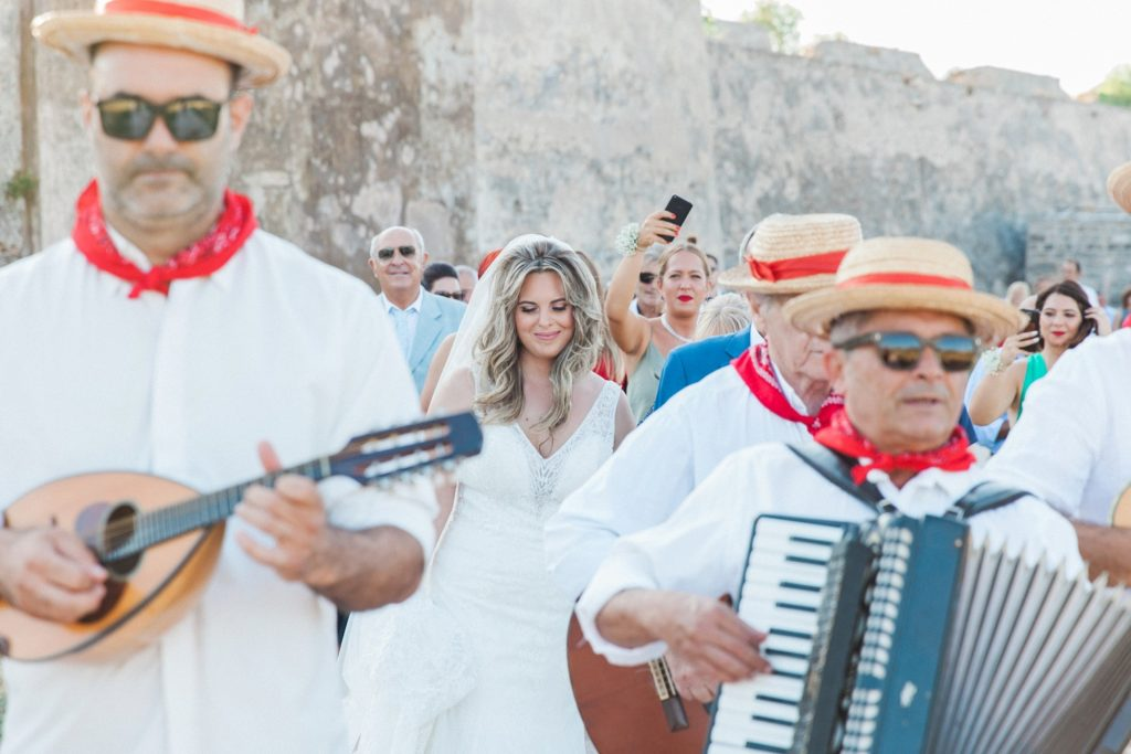 Bride smiles as the traditional Greek band leads her and her family to the church in Santa Maura Castle