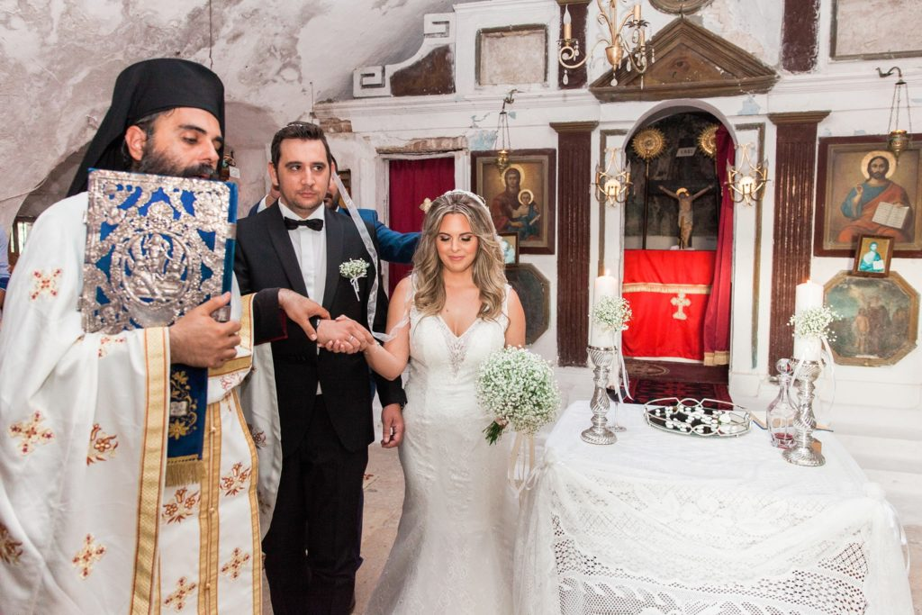 Couple make their way around the alter during their wedding ceremony at Santa Maura Castle in Lefkada