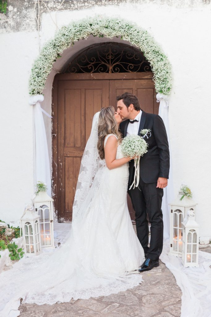Couple kiss in front of the door of the church inside Santa Maura Castle in Lefkada