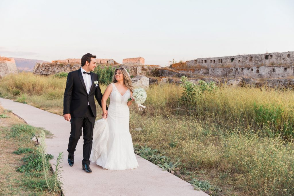 Happy couple makes their way through the grounds of the Santa Maura Castle in Lekfada