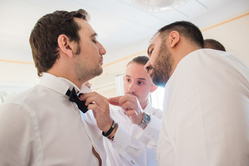 Groomsmen help the groom put on his bowtie on the morning of his wedding in Lefkada