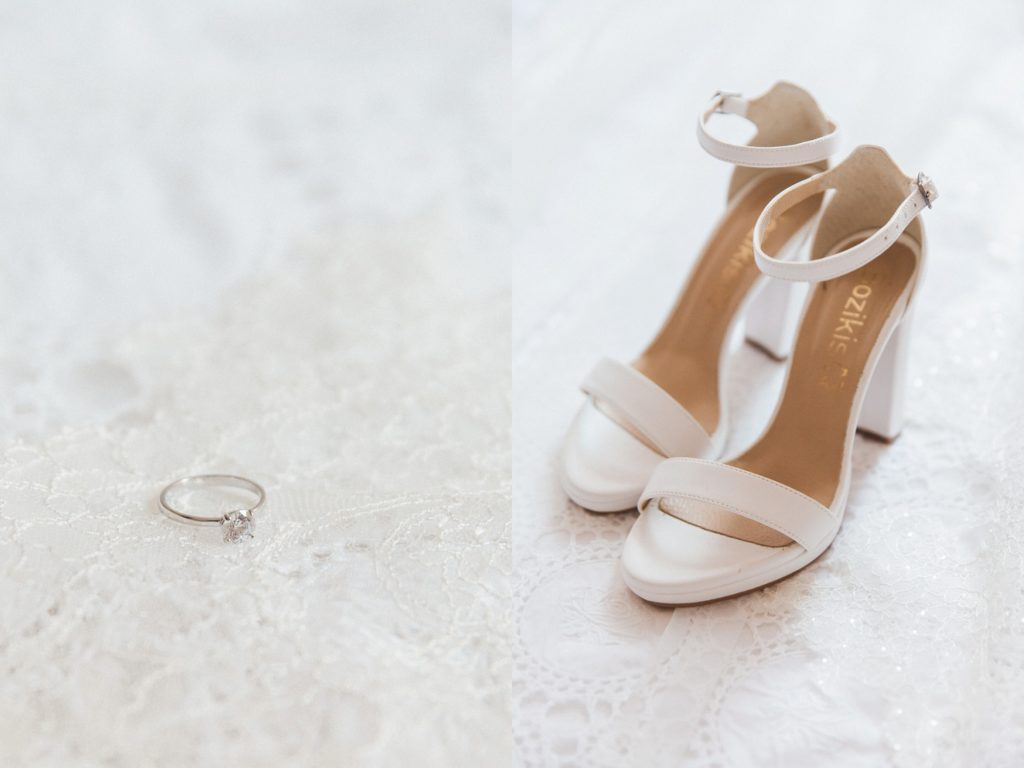 Diamond engagement ring and the brides wedding shoes on white lace