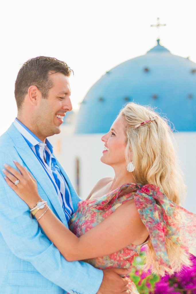 Happy couple hugging in front of a Greek church during their Santorini honeymoon photography session