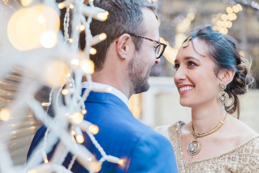 Portrait of a bride and groom amongst fairy lights in London