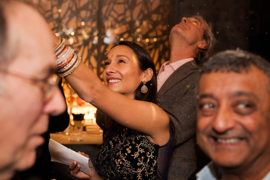 Guest smiles as she reaches up to the fake snow fall in the Secret Garden bar at South Place Hotel