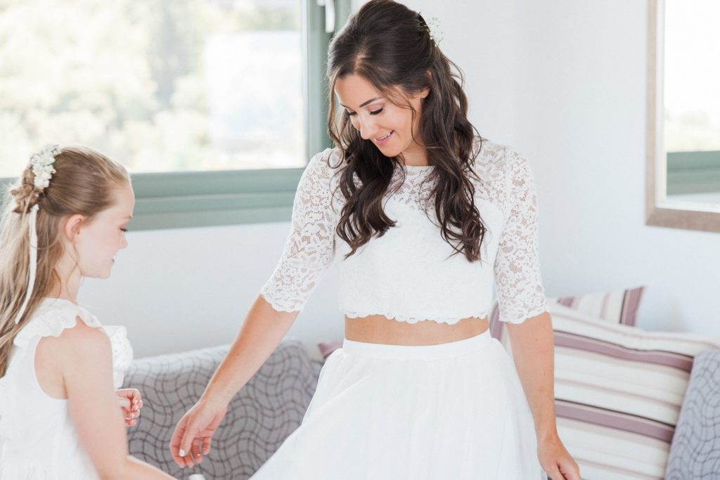 Bride and her daughter share a moment after putting on the wedding dress