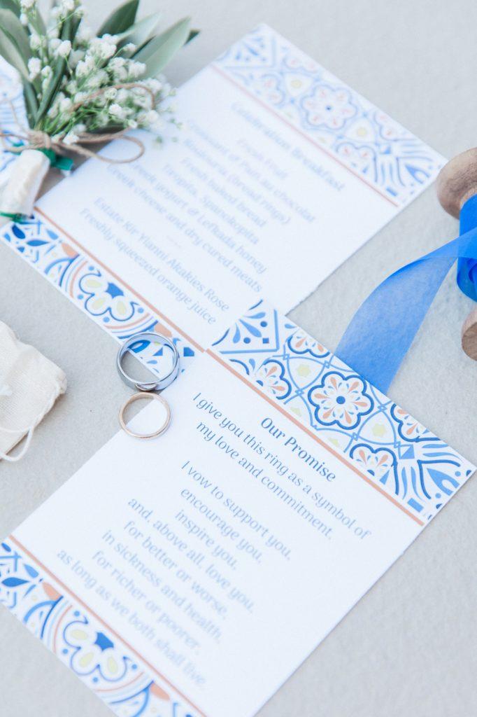 Blue, white and orange wedding stationery flatlay with wedding rings