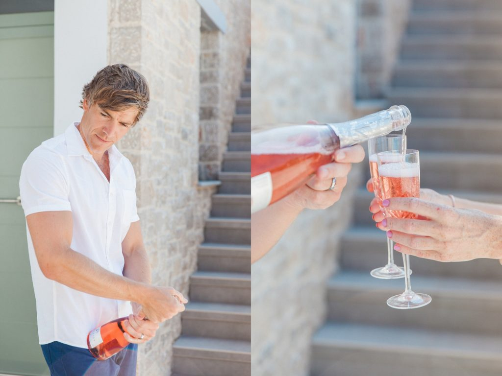 Groom opening and pouring pink prosecco