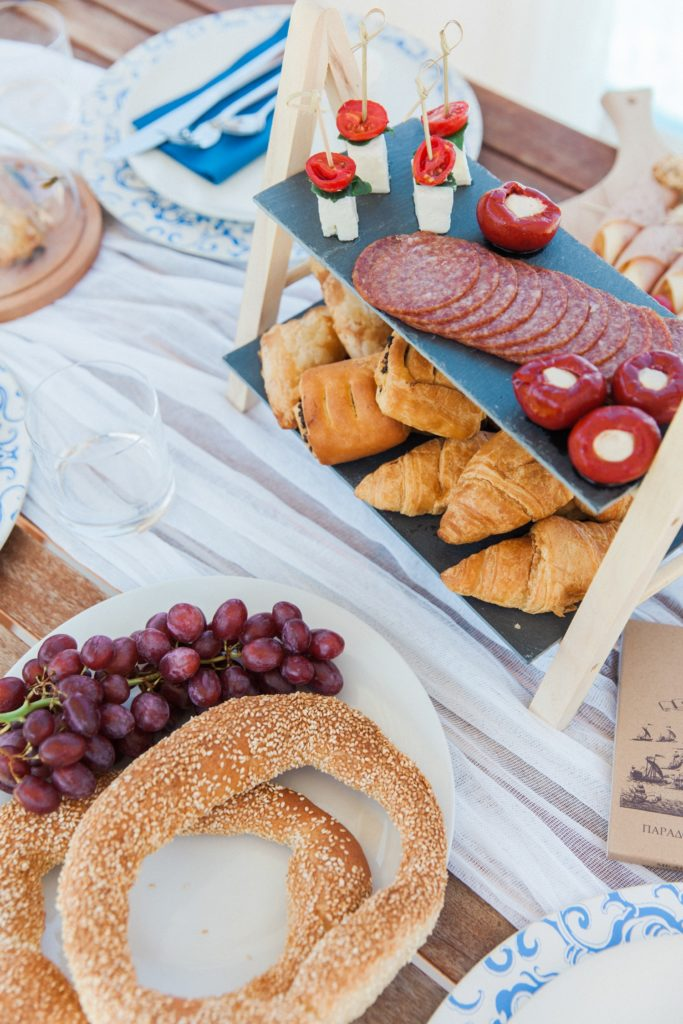 Picnic style wedding breakfast with pastries, meats, stuffed peppers and fruit
