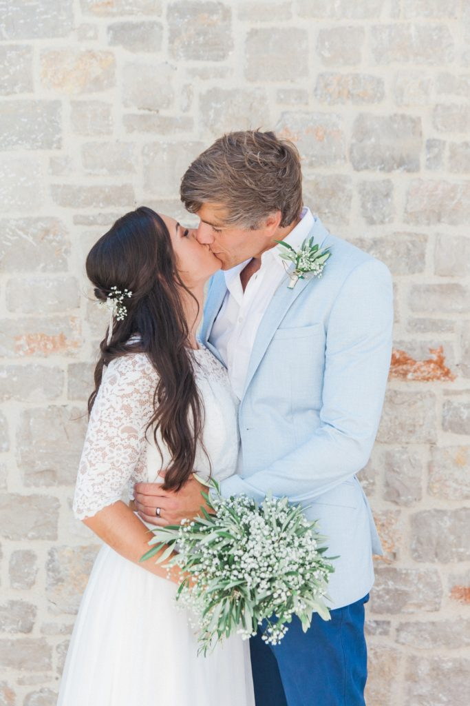 Happy couple kiss after their destination elopement in a villa on Lefkada