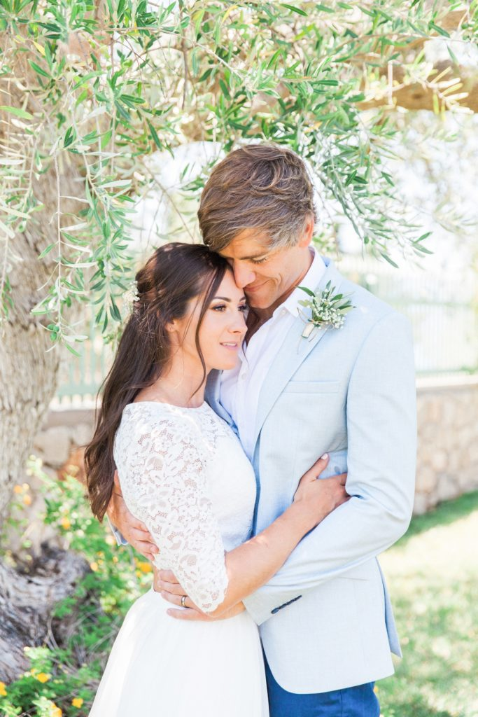 Bride and groom under the olive trees after their villa elopement