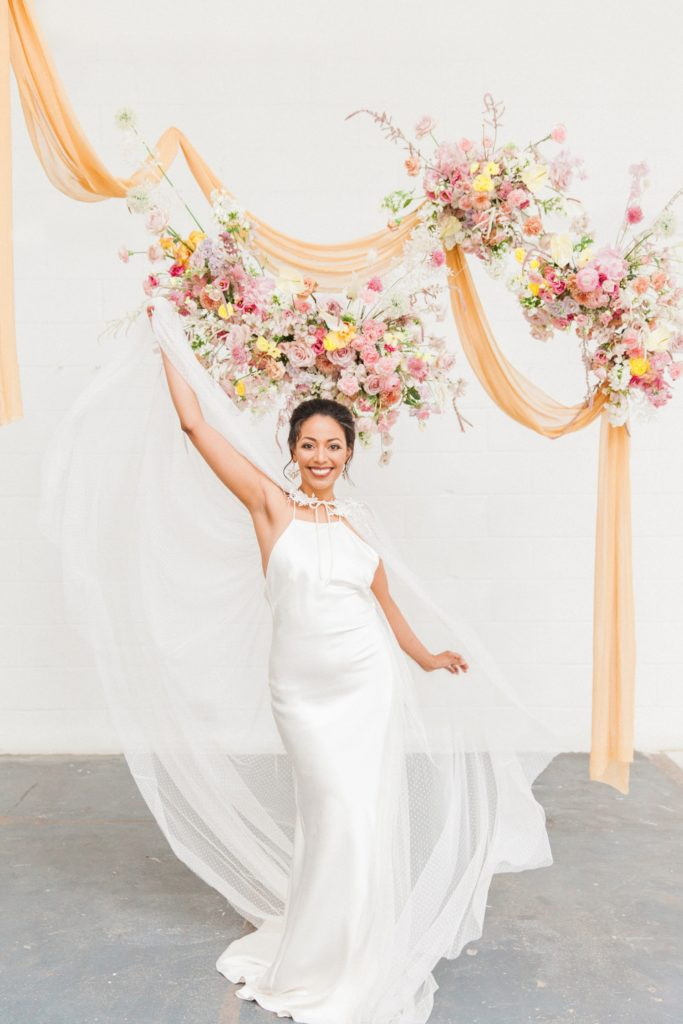 Black bride in a Halfpenny London wedding gown dances under colourful flower clouds