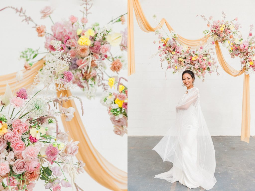 Spring inspired hanging flower arrangements above a bride wearing a Halfpenny London gown
