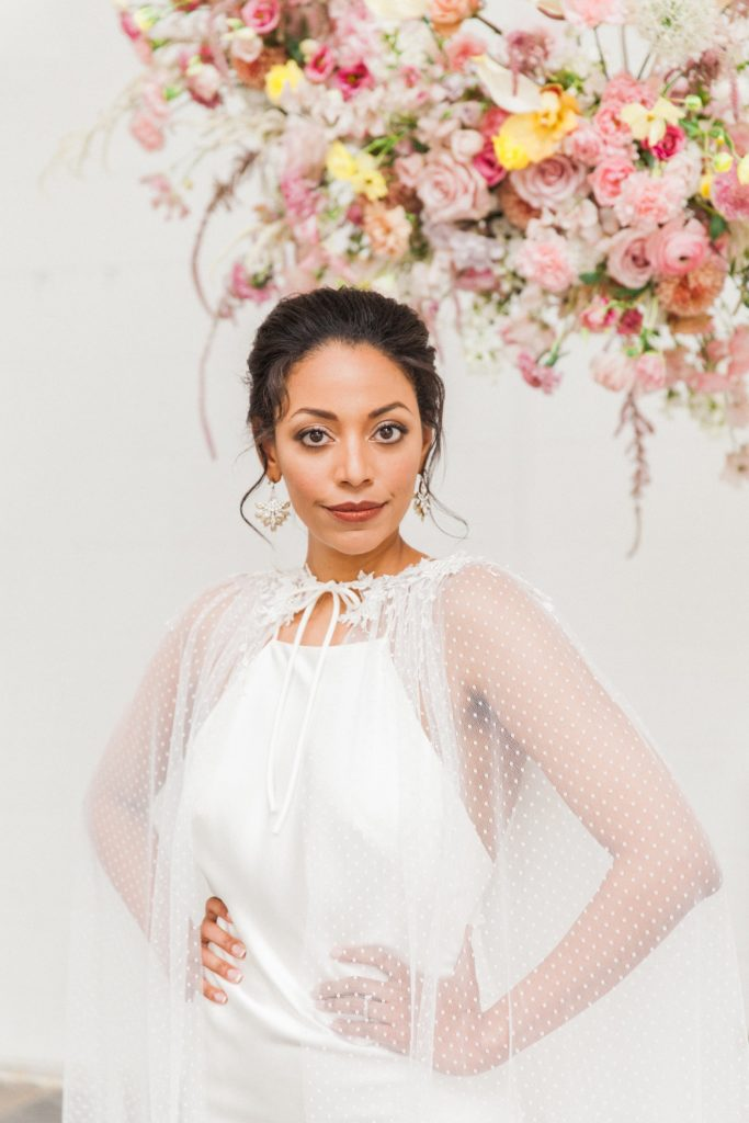 Portrait of a bride wearing a Halfpenny London wedding gown under a spring inspired hanging flower arrangement