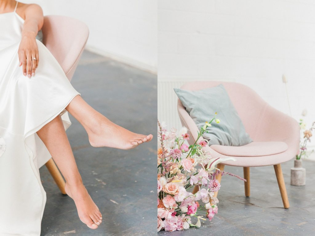 Colourful spring wedding flowers on the floor next to a bride with her feet up in a pink chair