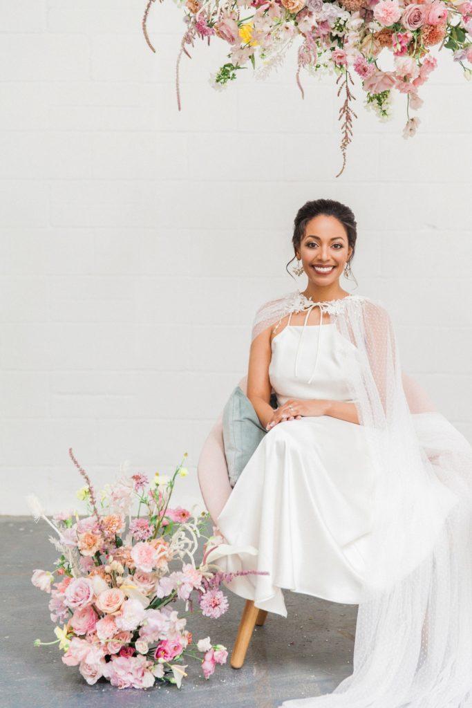 Bride smiles as she sits under a spring inspired hanging flower arrangement
