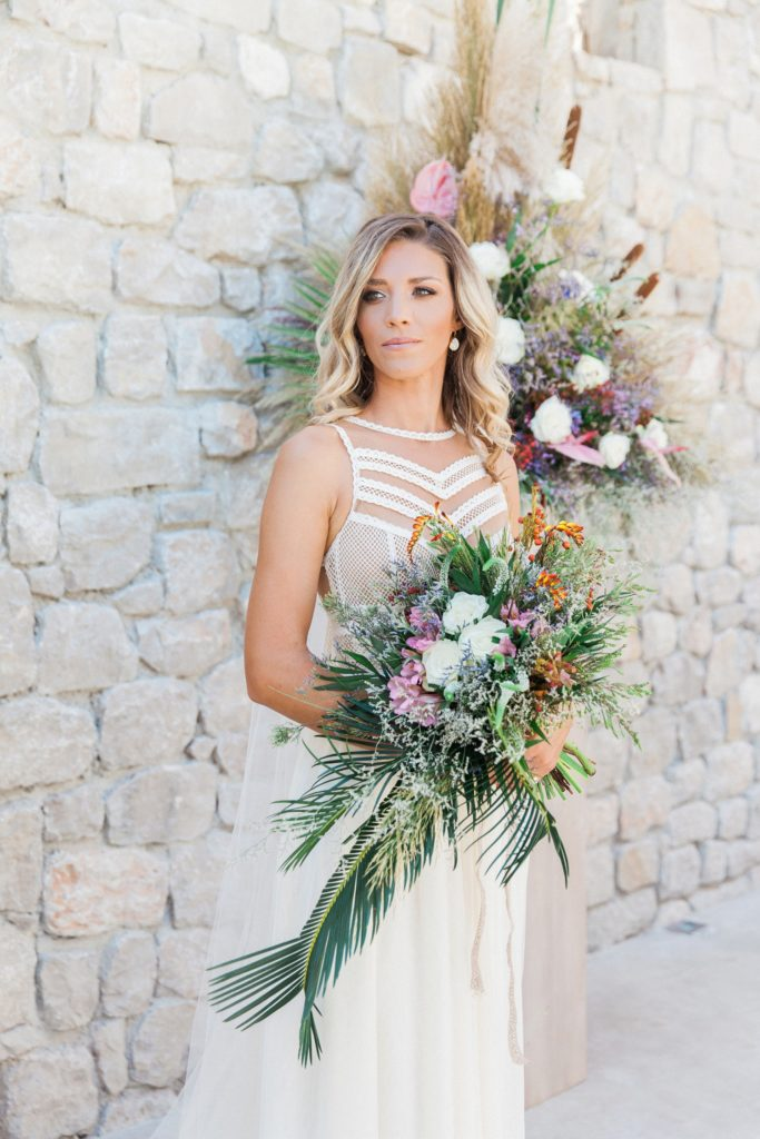 Boho bride poses with her bouquet in her wedding ceremony area at Crystal Waters Lefkada
