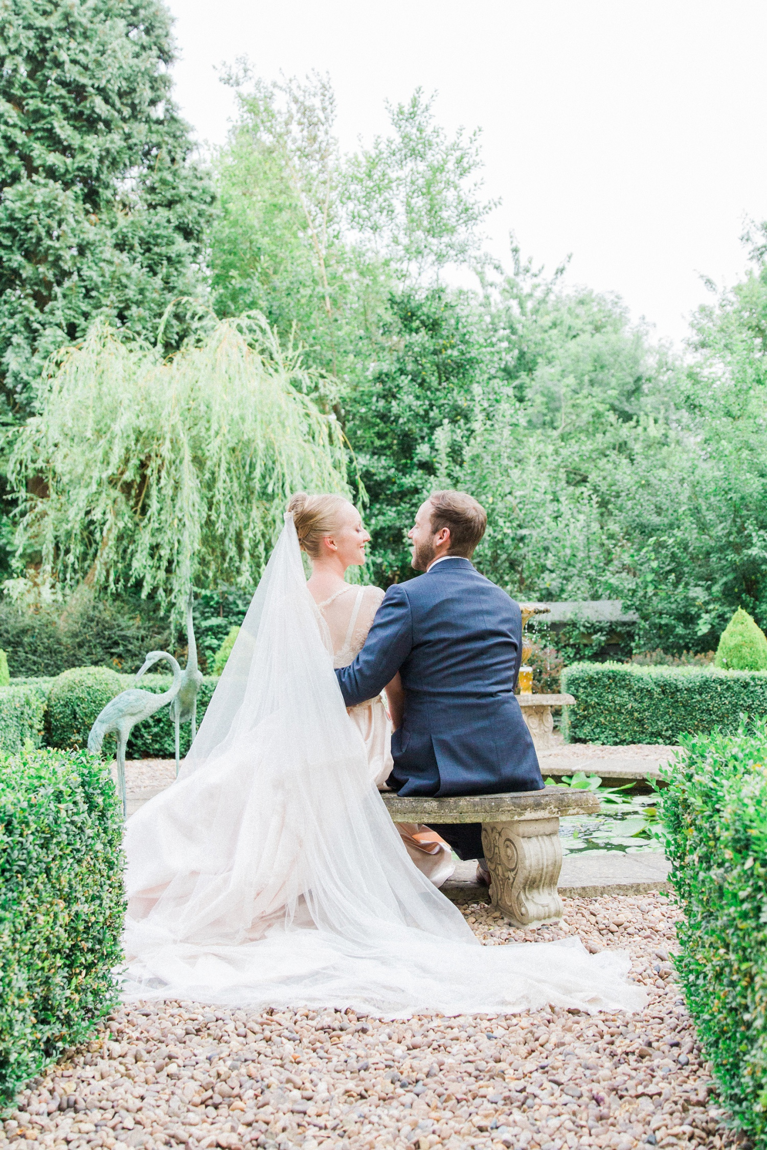 Bride and groom sit on a bench together during their English garden wedding