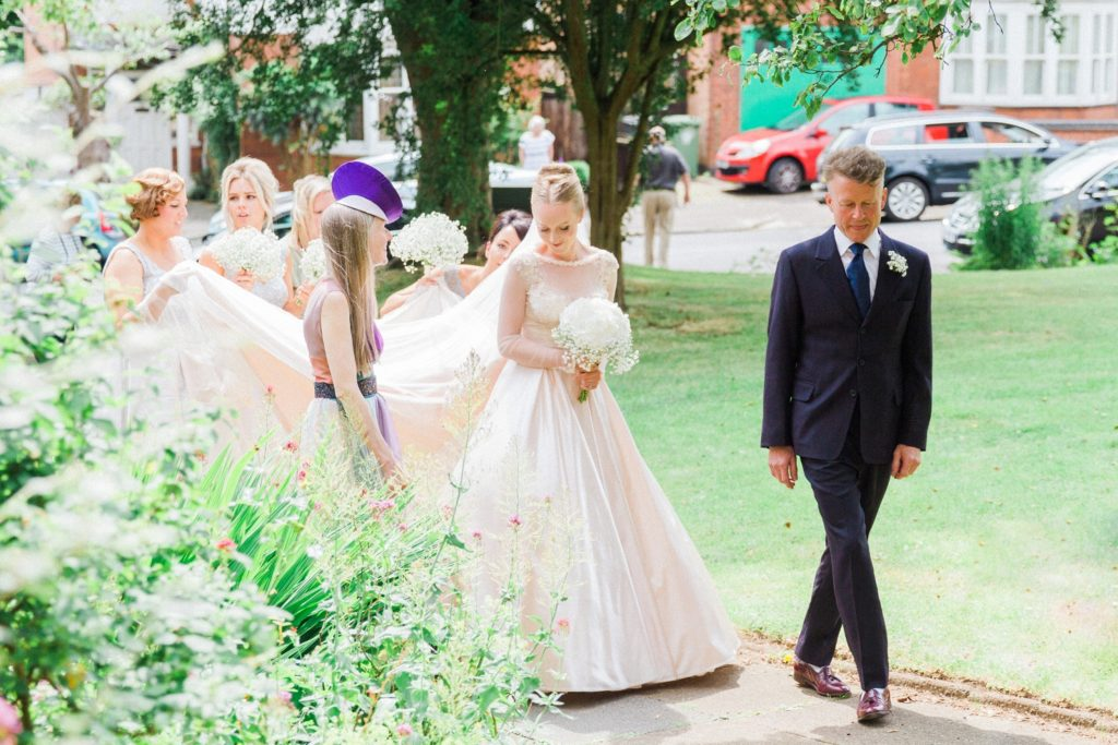 Bride and her bridal party walk through the church gardens on the morning of her wedding