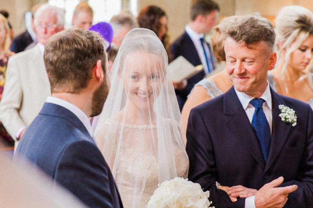 Bride smiles at the groom as she arrives at the top of the aisle