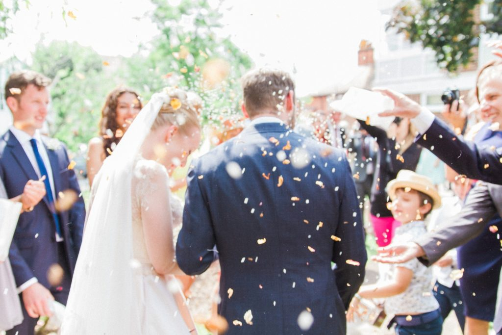 Couple walk through a shower of confetti on their wedding day