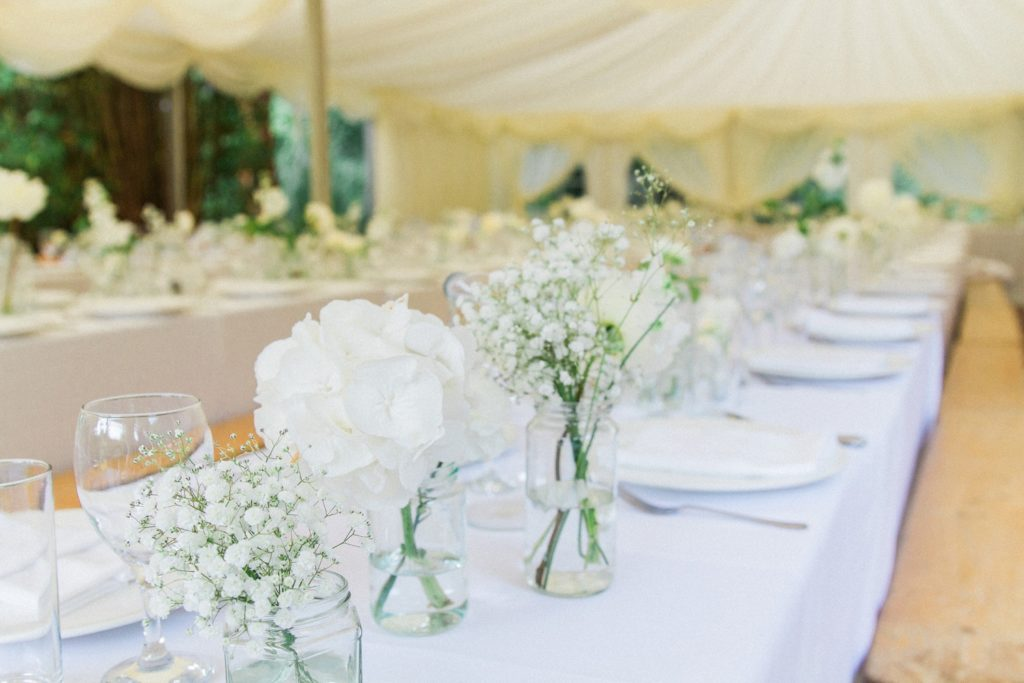 White flowers in small vases down the centre of the wedding tables in a private garden in Leicestershire