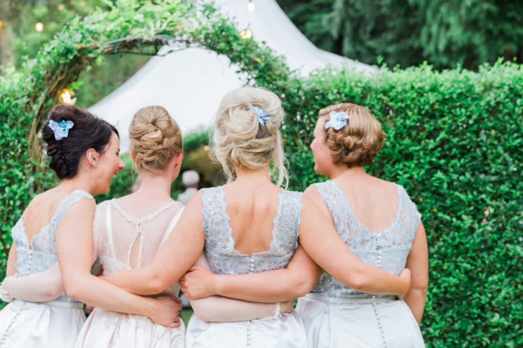 Bride and bridesmaids make their way to the marquee wedding reception in the garden