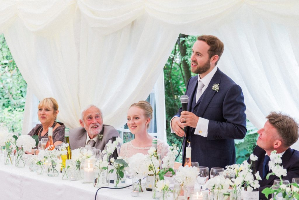 Groom says his speech at a marquee wedding in the garden