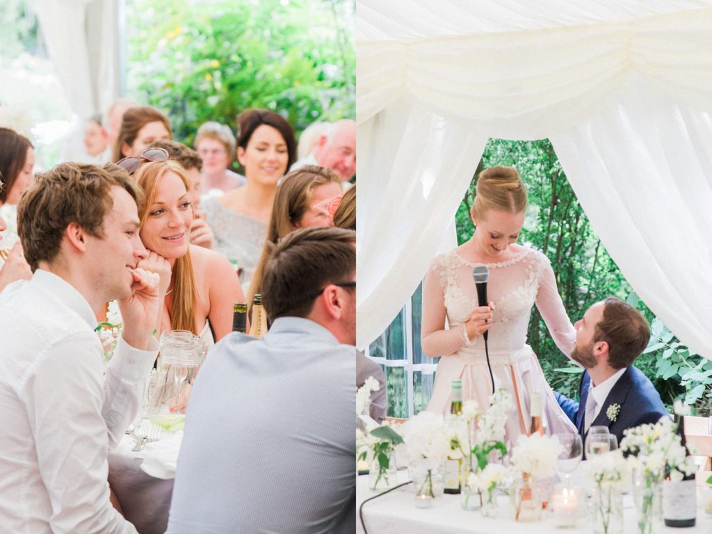 Wedding guests smile as the bride says a speech at her marquee wedding in the garden