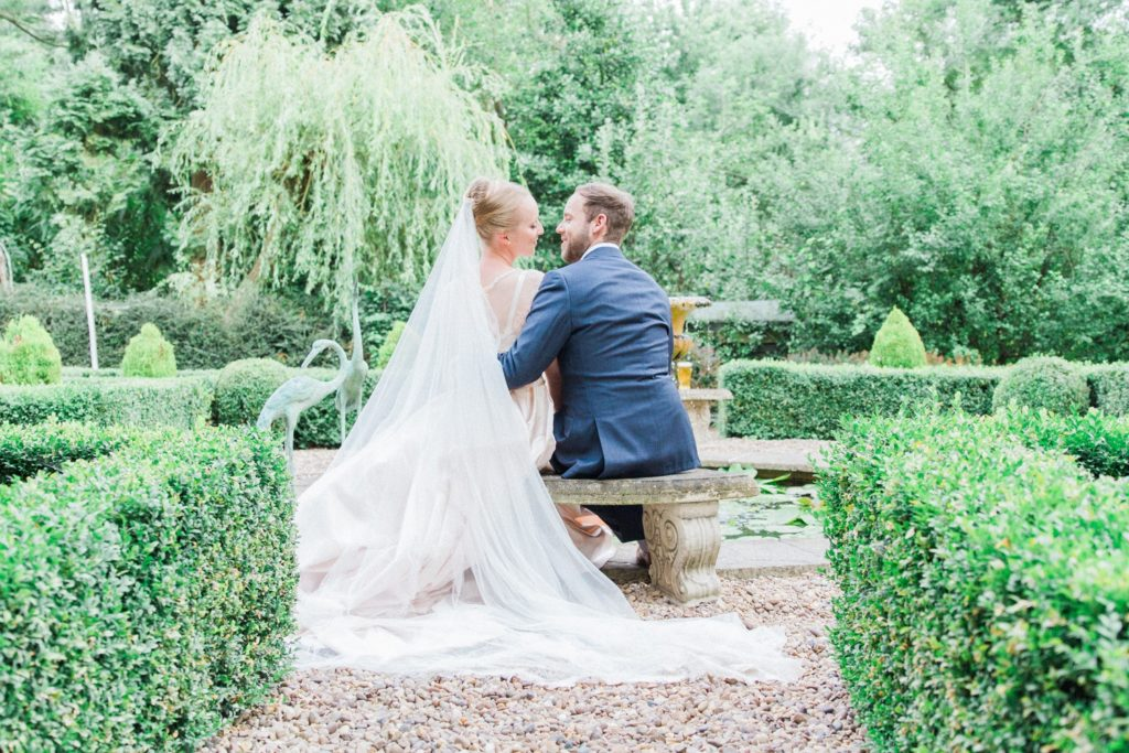 Bride and groom sit together in the garden on their wedding day