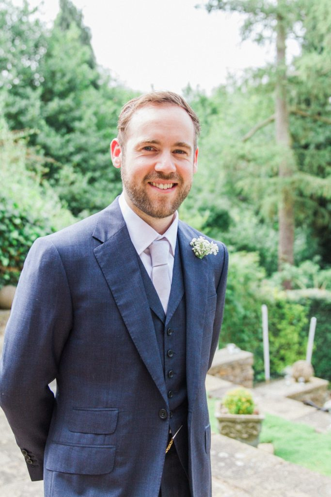 Groom smiles in the garden on the morning of his wedding