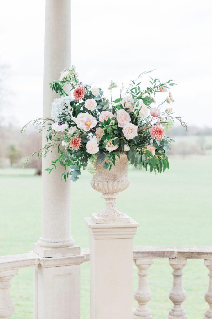 Pastel flower arrangement in an urn for a Beatrix Potter inspired wedding at Froyle Park