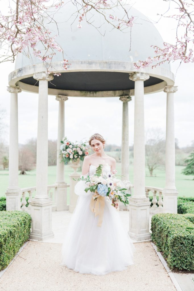 Bride holds a pastel bouquet in front of the wedding gazebo at Froyle Park