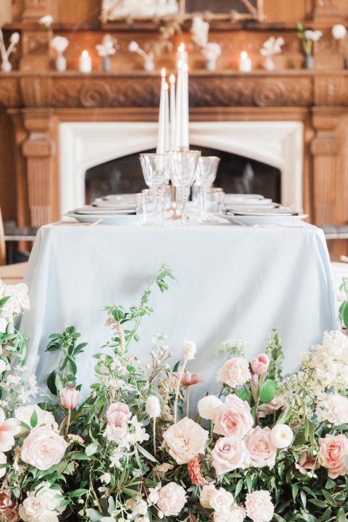 Wild flower floor arrangements and pastel table decor at a Froyle Park wedding