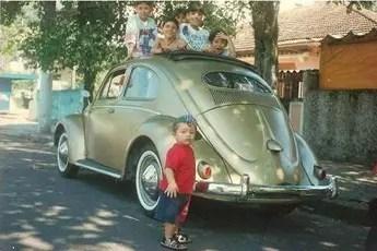 O Lauro Defesa Jr. aparece nesta foto de 1997 com uma blusa vermelha, ele tinha 2 anos de idade. O Fusca oval 1954 tinha teto solar de pano original