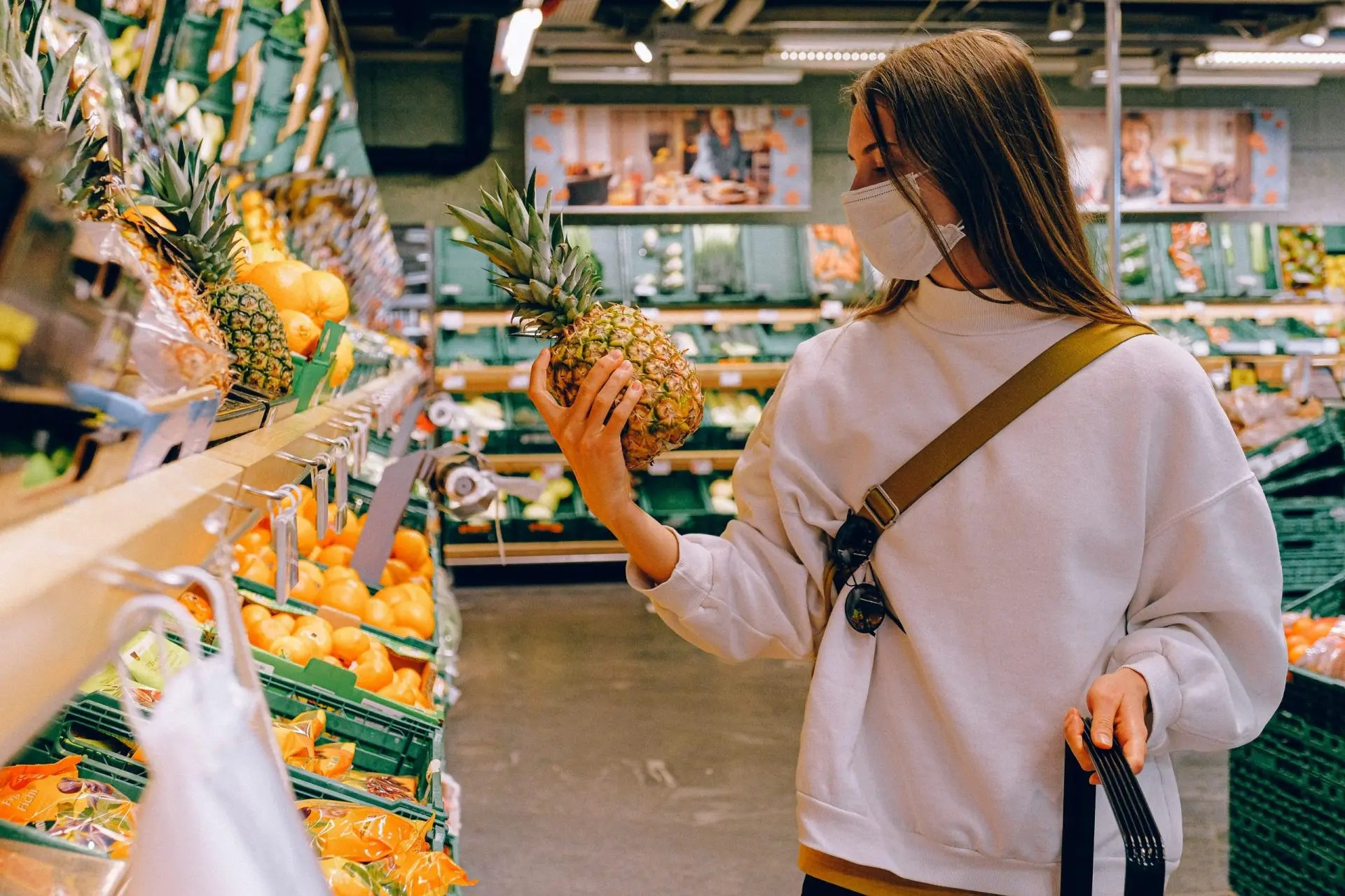 Woman wearing a mask, holding a pinaple, in supermarket