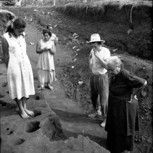 Jack Golson excavating in Vailele, north coast of Upolu island in Samoa, 1957. Visiting the site are members of the I'iga Pisa family.