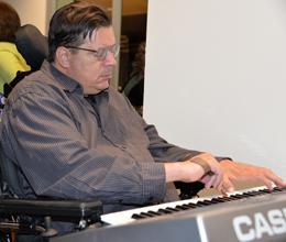 John Kraimer, a ThinkFirst Voice for Injury Prevention, plays the keyboard with the help of a typing stick.