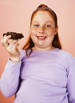 Overweight Child Eating Junk Food --- Image by © moodboard/Corbis