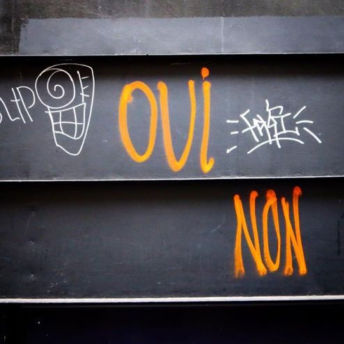 Oui Non graffiti spray art in Paris, France, orange against a black door